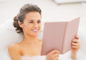 Happy young woman in bathtub reading book