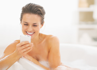 Young woman in bathtub writing sms