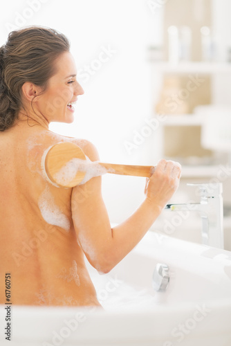 Smiling young woman in bathtub using body brush