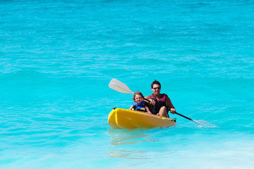 Father and son on a kayak ride in a tropical ocean