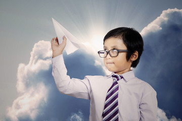 Little businessman throwing a paper plane