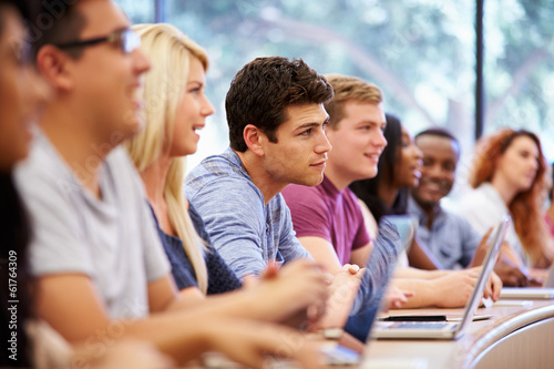 Class Of University Students Using Laptops In Lecture - 61764309