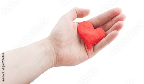 Red cloth heart in hand. Selective focus on heart.