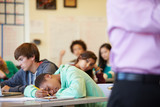 Bored High School Pupil Slumped On Desk In Classroom