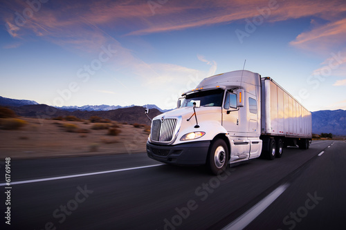 Truck and highway at sunset - transportation background poster