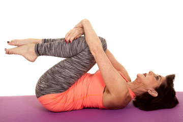 older woman yoga on back curl knees