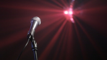 Microphone on stage against the rotating multicolor disco ball