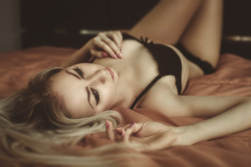 Young attractive  blond woman in sexy lingerie posing in bed. Vo
