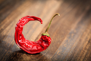 Bent red hot chilli pepper on a table