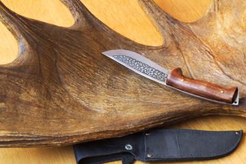 Hunting knife sheath and a trophy hunter - big elk horn.
