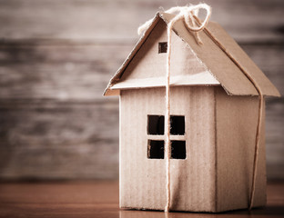 house in brown recycled paper on wooden background