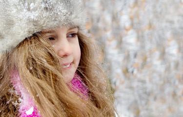 Happy little girl in warm hat - closeup portrait