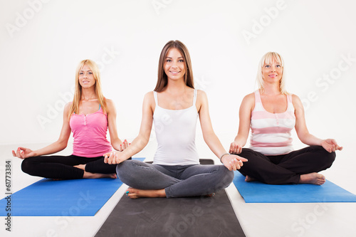 Three beautiful women sitting in lotus position.