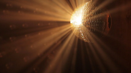 Shiny disco ball with golden reflection and rays in haze, HD 108