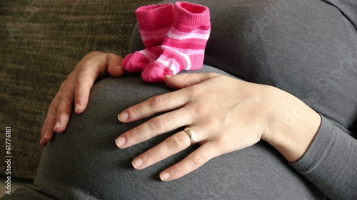 Pregnant woman with baby socks touching belly