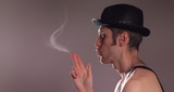 Man in retro hat blows onto a smoke