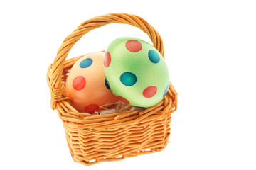 Small basket with easter eggs on white