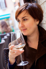 Portrait of young smiling woman with glass of white wine