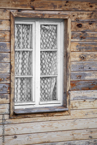 Rural much neglected window in wooden wall, wooden background
