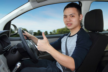 A young man showing thumbs up while driving