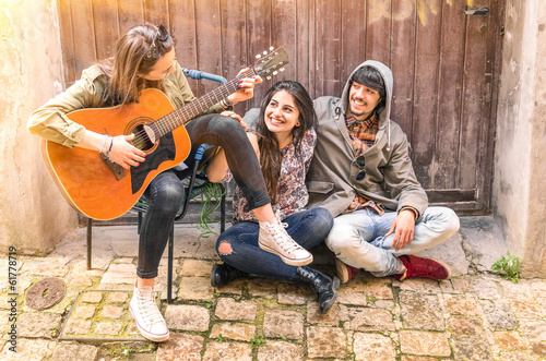 Teenagers playing guitar and having fun outdoors