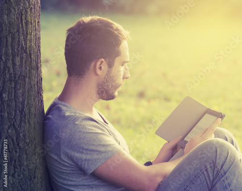 Young man reading e-book