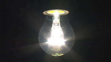 real light bulb is turning on, black background, Slow-Motion, HD
