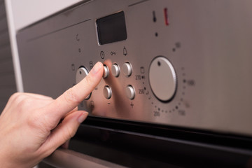 Girl's hand push the oven's button