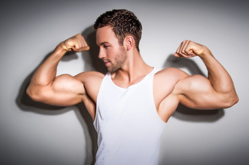 Portrait of a healthy young man showing his arms