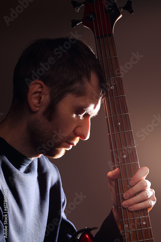 Portrait of man with guitar in backlight