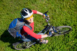 Young cyclist  on green grass