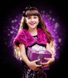 Girl holding the present box on dark background