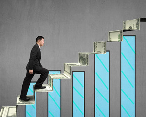 businessman walking on money stairs with chart