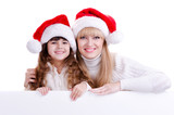 Mother and daughter is Santa hats holding a blank board