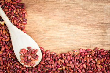 Red beans and a spoon framing a wooden background