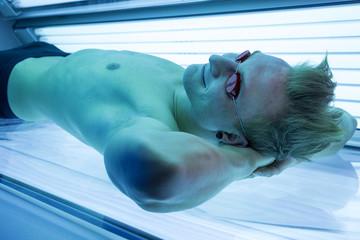 Man in solarium enjoying sunbathing on tanning bed