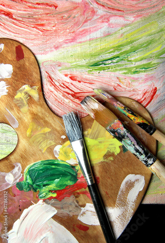 Art palette, paintbrushes and picture with flowers