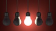 Glowing light bulb among dead ones hanging on red