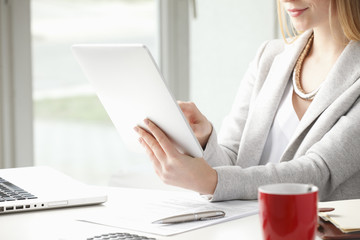 Close-up of businesswoman is typing on her tablet