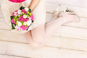 Bride's legs and flowers on wooden floor