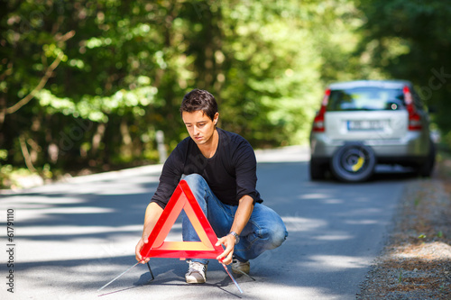 Handsome young man with his car broken down by the roadside