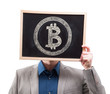 Businessman hiding his face behind bitcoin symbol