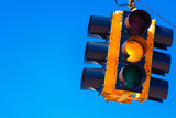 Fototapety A yellow traffic light with a sky blue background