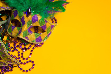 Colorful group of Mardi Gras or venetian mask on yellow