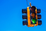 A green traffic light with a sky blue background