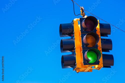 Leinwanddruck Bild A green traffic light with a sky blue background
