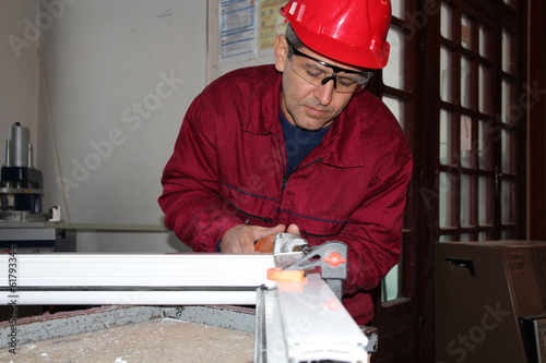 Worker Using Electric Grinder.
