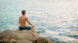 Young man practicing yoga. Sits in a lotus position on the ocean