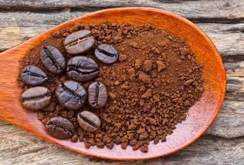 Roasted coffee beans and ground coffee in wooden spoon on textur