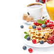 delicious breakfast with waffles, berries, orange juice
